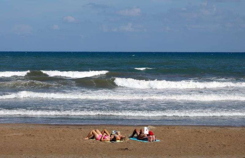 Tres personas toman el sol, esta tarde en la playa de la Malvarrosa de Valencia. EFE/Archivo