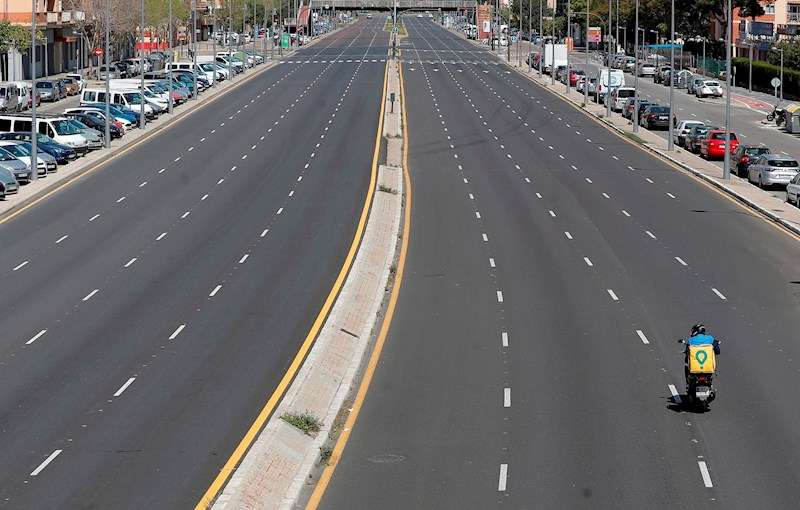 Un repartidor circula por una avenida desierta de València durante el estado de alarma, en una imagen reciente. EFE