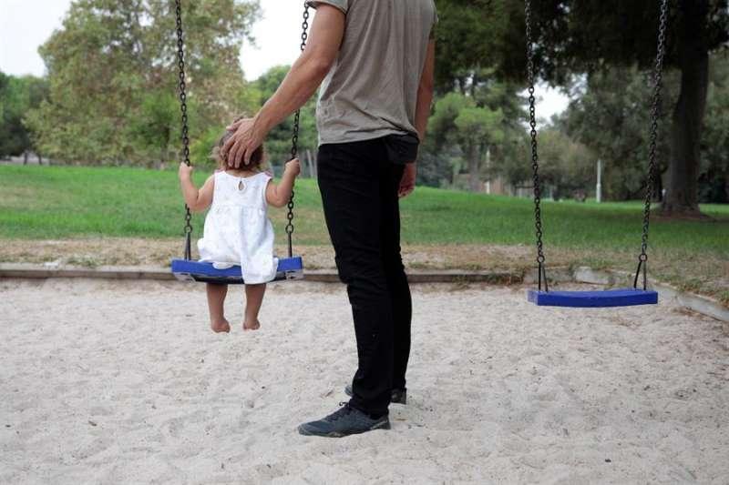 Una persona juega con una niña en un columpio. EFE/Biel Aliño