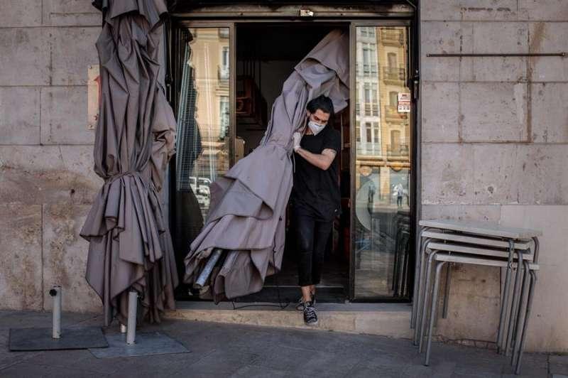 En la imagen, un trabajador monta la terraza de una cafetería en València. EFE