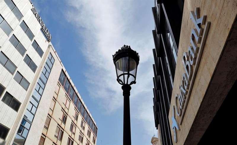 El logo de Caixabank sustituye al de Bankia tras la fusión de ambos bancos en lo que era la sede social de esta última entidad en Valencia. EFE