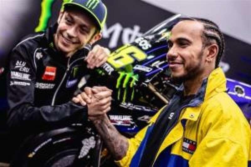 Valentino Rossi (i) y Lewis Hamilton (d) se saludan tras anunciar su reto. EPDA