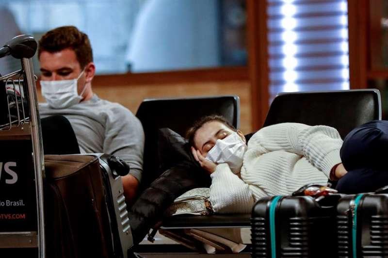Varias personas durmiendo en un aeropuerto con mascarilla. EFE/Archivo