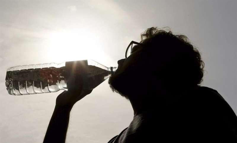 Una persona bebe agua en una calle de València. EFE