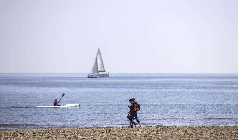 Un hombre navega en su kayak cerca de la orilla de la playa de La Malva-rosa de València, mientras una pareja disfruta de las temperaturas suaves. EFE/Archivo