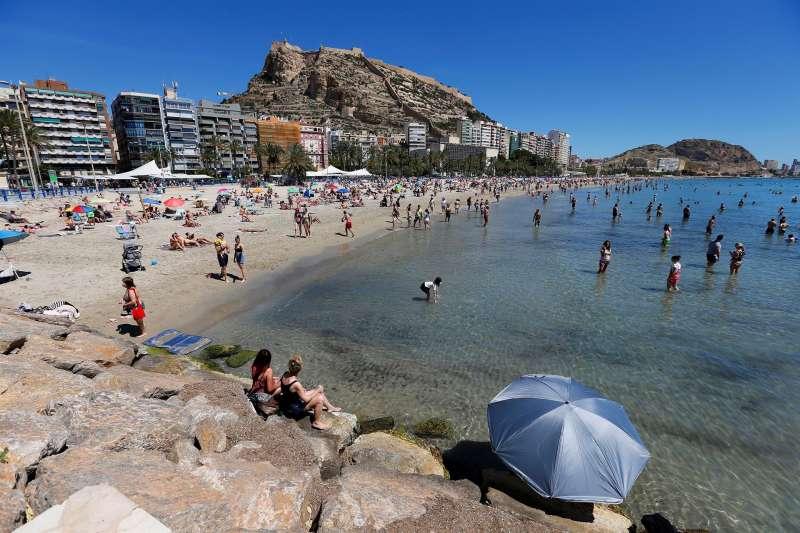 Bañistas disfrutan de un día de buen tiempo en la playa del Postiguet, en Alicante.