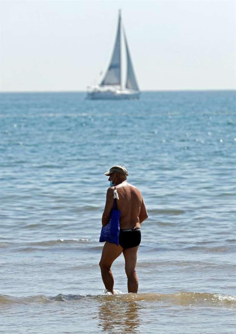 Un hombre se refresca en las aguas de la playa de la Malvarrosa. EFE