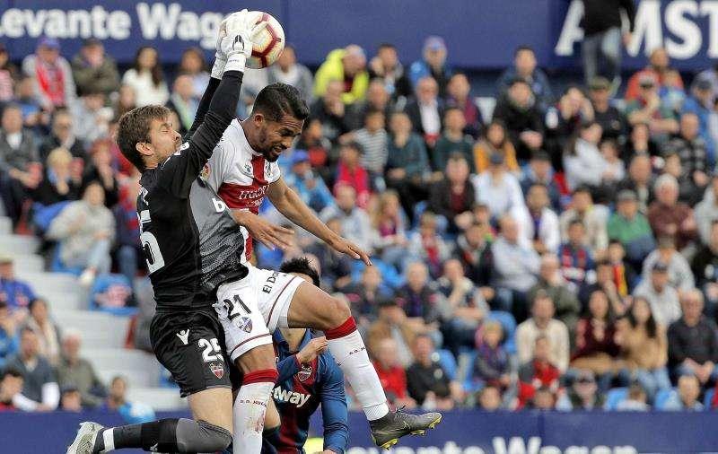 El portero del Levante Aitor Fernández (i) atrapa un balón ante el centrocampista del SD Huesca, Yanguel Herrera. EFE/Archivo