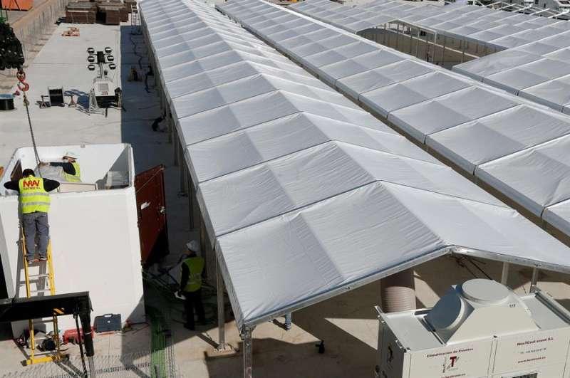 Varios operarios trabajan en la estructura del hospital de campaña de València, con 500 camas, que se está levantando junto al hospital La Fe, en una imagen de este viernes. EFE/ Kai Försterling