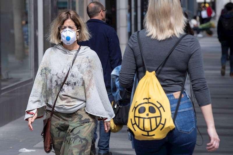 Un mujer se protege del coronavirus con una mascarilla. EFE