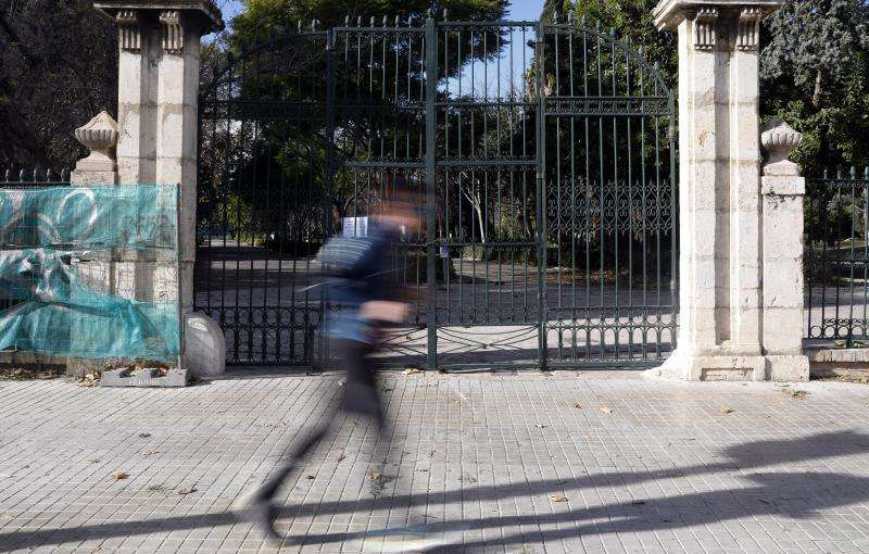 Imagen de archivo de un hombre corriendo ante la puerta principal de los Jardines del Real cerrados por fuerte viento. EFE/Archivo