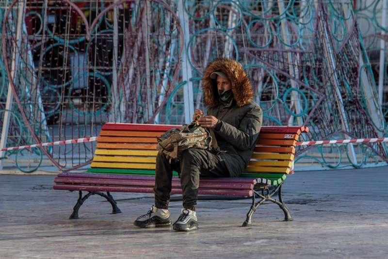 Una persona sentada en un banco en València se protege del frío. EFE/Biel Aliño/Archivo
