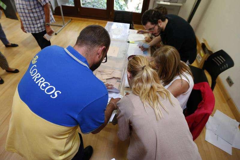 Un funcionario de Correos entrega en una mesa electoral los votos por correo. EFE/Archivo