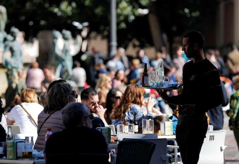 Un camarero atiende una terraza, en la plaza de la Virgen de Valencia, llena de clientes en una imagen del pasado mes de febrero. EFE/Manuel Bruque