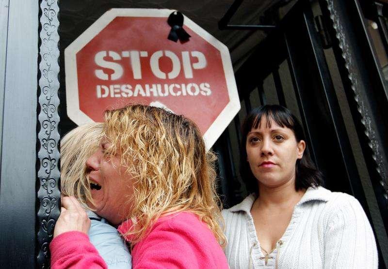 Dos personas se abrazan en el transcurso de un desahucio. EFE/Cárdenas/Archivo