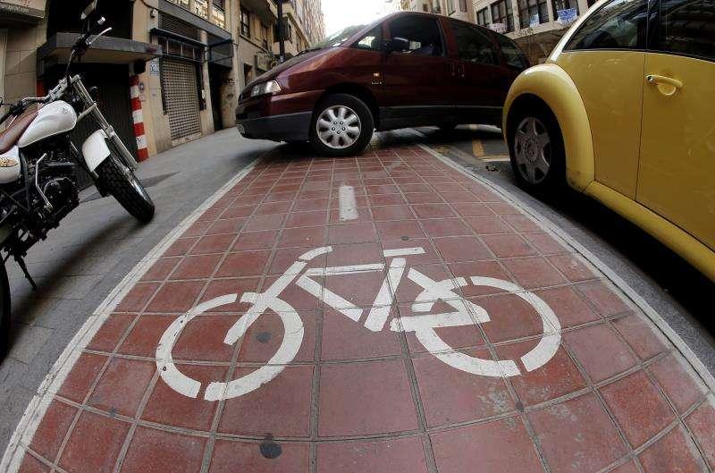 Un coche invade un carril bici en València para entrar a un garaje. EFE/Archivo