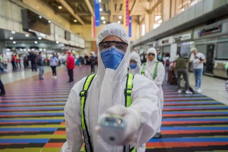 Un trabajador sanitario muestra un termómetro en un aeropuerto. EFE/Archivo