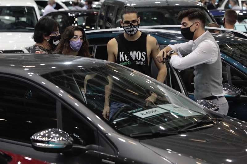 Un vendedor muestra un vehículo a varios clientes en la Feria del Vehículo de Ocasión. EFE/Biel Aliño