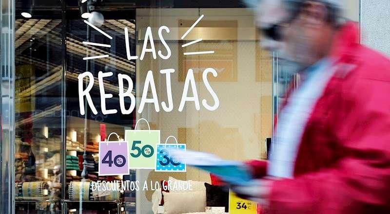 Un hombre pasa ante el escaparate de una tienda que ofrece descuentos de hasta el 50% en el inicio de las rebajas