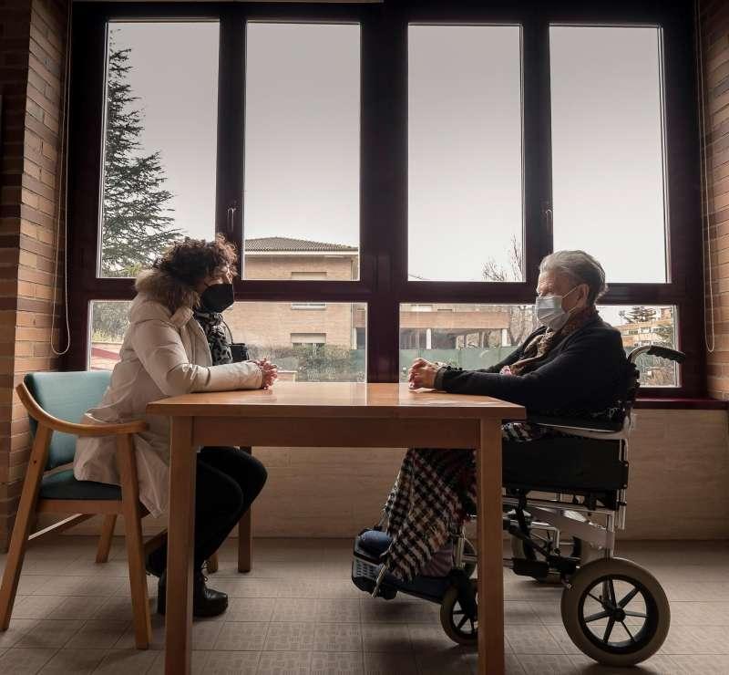Una mujer visita a su madre en una residencia.