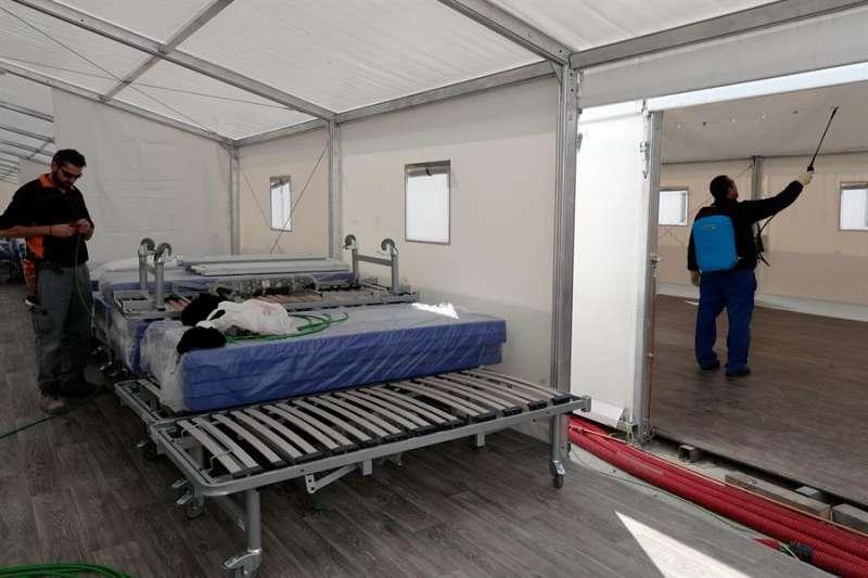 Operarios ultiman el montaje del hospital de campaña. EFE/Kai Försterling