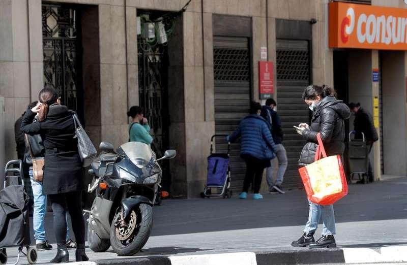 Varias personas guardan cola para realizar la compra en un supermercado. EFE