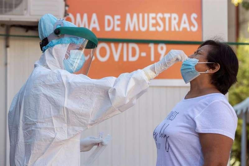 Una enfermera toma una muestras para una prueba PCR a una mujer. EFE/Archivo