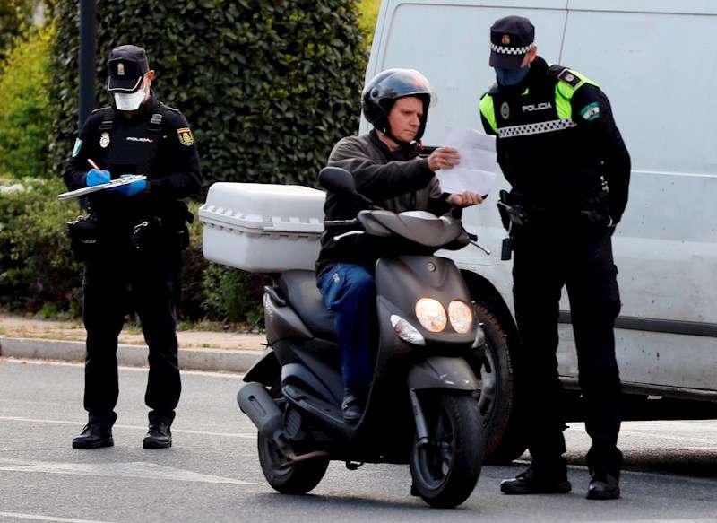 Efectivos de la Policía Nacional y de la Policía Local realizando hoy un control de seguridad por el confinamiento obligatorio. EFE