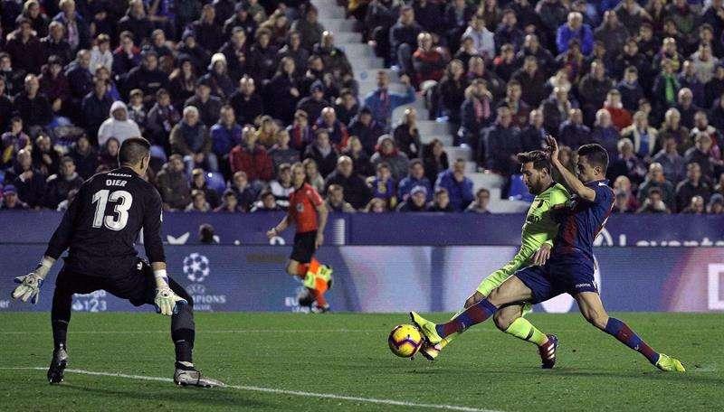 El delantero del FC Barcelona Leo Messi (c) chuta ante Postigo y el portero Oier (i) para marcar el segundo gol ante el Levante, durante el partido de Liga en Primera División en el estadio Ciutat de Valencia. EFE