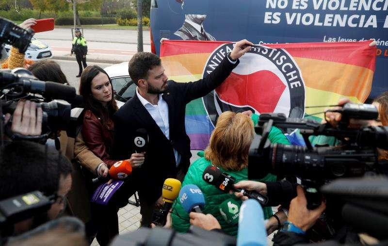 Un miembro de HazteOír atiende a los medios ante el autobús que pretendía circular ayer por la ciudad con los lemas #StopFeminazis. No es Violencia de Género, es Violencia Doméstica, pegados por todo el vehículo, y que la Policía Local de València condujo a la central policial. EFE