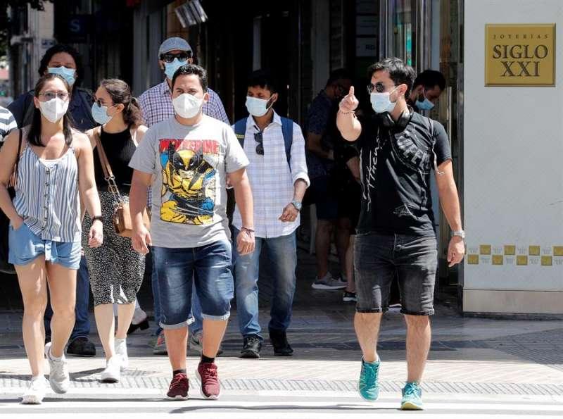 Transeúntes protegidos con mascarillas pasean por una céntrica calle de Valencia. EFE/ Juan Carlos Cárdenas/Archivo