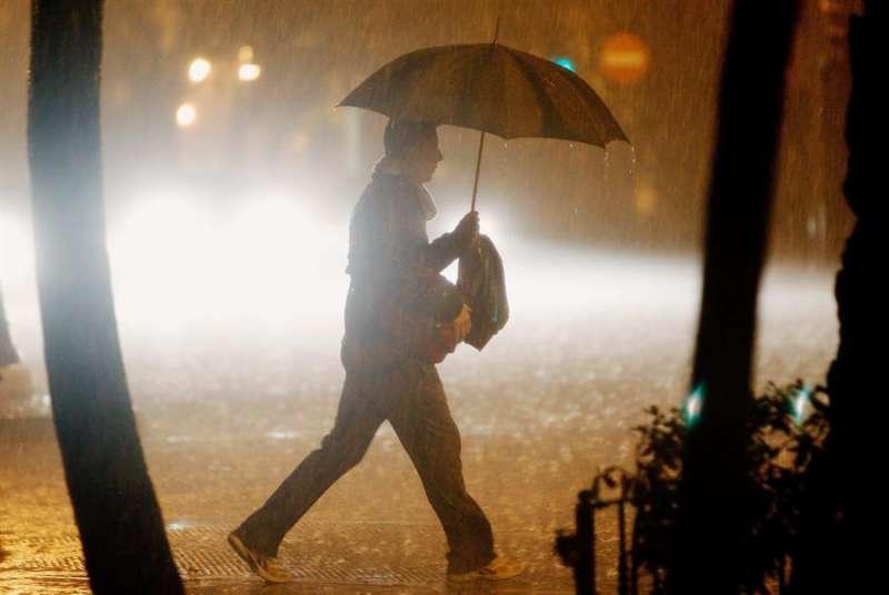 Una persona camina bajo la lluvia. EFE/Kai Försterling/Archivo