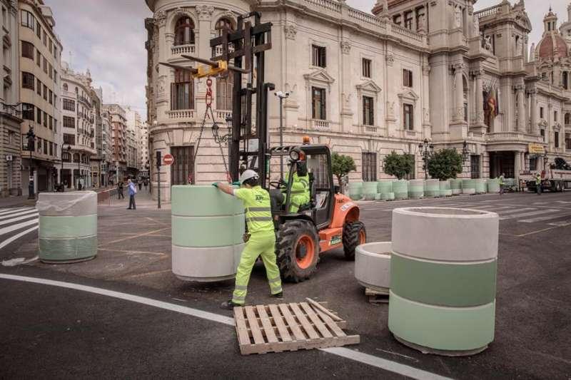 Varios operarios trabajan en la peatonalización de la plaza del ayuntamiento de València. EFE/Biel Aliño