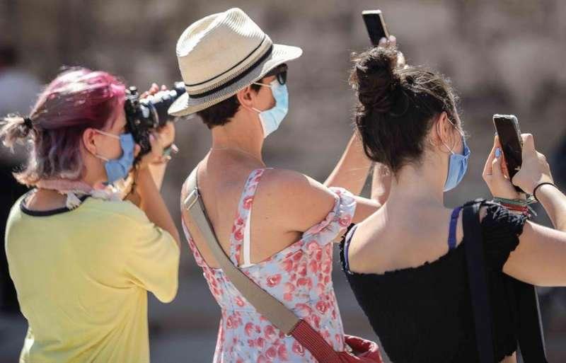 Varias turistas toman fotografías en València, en una imagen del pasado verano. EFE/Ana Escobar