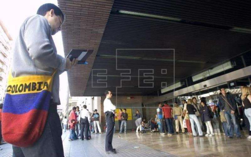 Un hombre revisa unos papeles junto a la cola de extranjeros que esperan ante una de las oficinas del Instituto Nacional de la Seguridad Social. EFE/Archivo