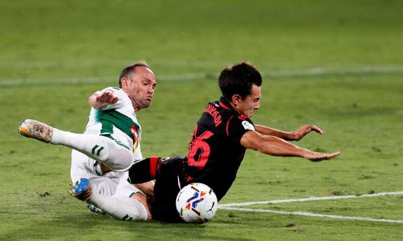 El delantero del Elche Nino (i) cae junto a Zubimendi, de la Real Sociedad, durante el partido de Liga en Primera División disputado este sábado en el estadio Martínez Valero, en Elche. EFE/Ramón