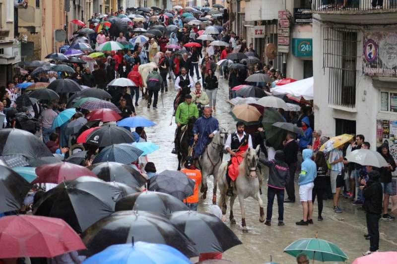 Los jinetes regresando a las cuadras entre paraguas