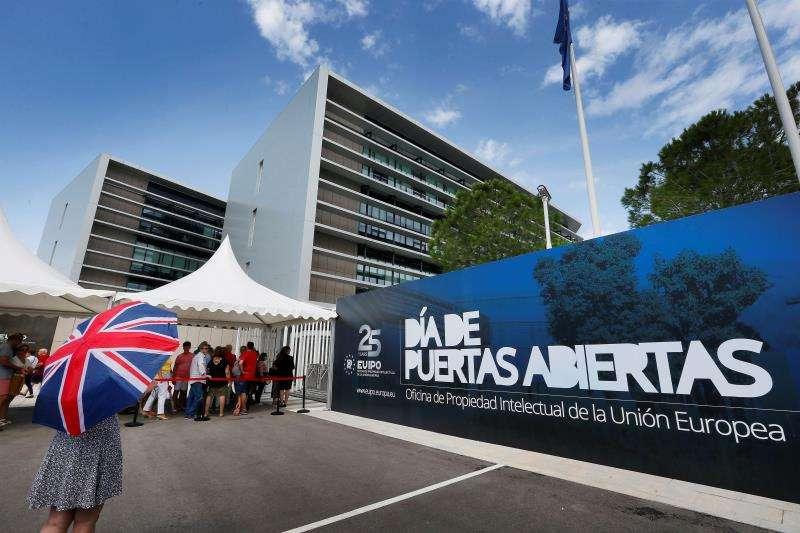 Miles de asistentes han acudido este sábado a las instalaciones de la EUIPO en el 25 aniversario de la Oficina de Patentes de la Unión Europea. Una visitante con un paraguas con la bandera británica hace cola a las puertas de las instalaciones. EFE/Manuel Lorenzo