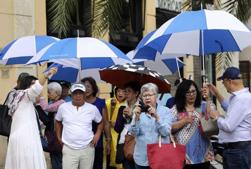 Unos turistas, protegidos con paraguas, recorren el centro de la ciudad de València. EFE/Archivo