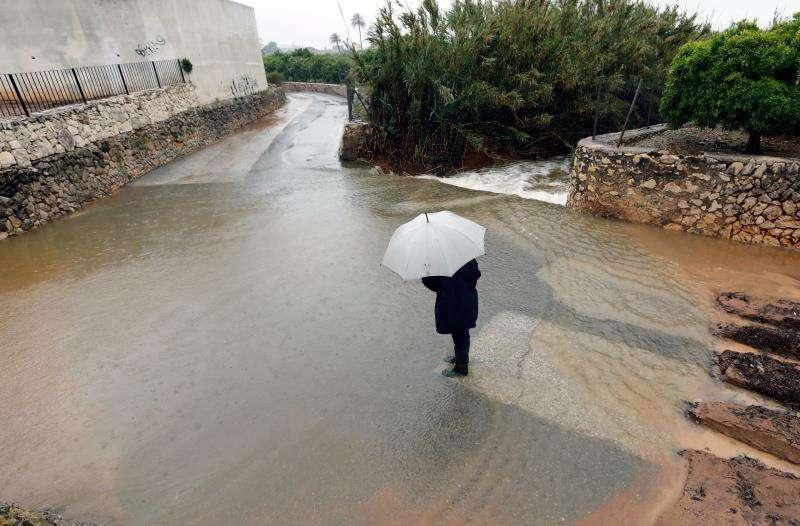 Una persona se protege de un reciente temporal en Alicante con un paraguas. EFE/Archivo