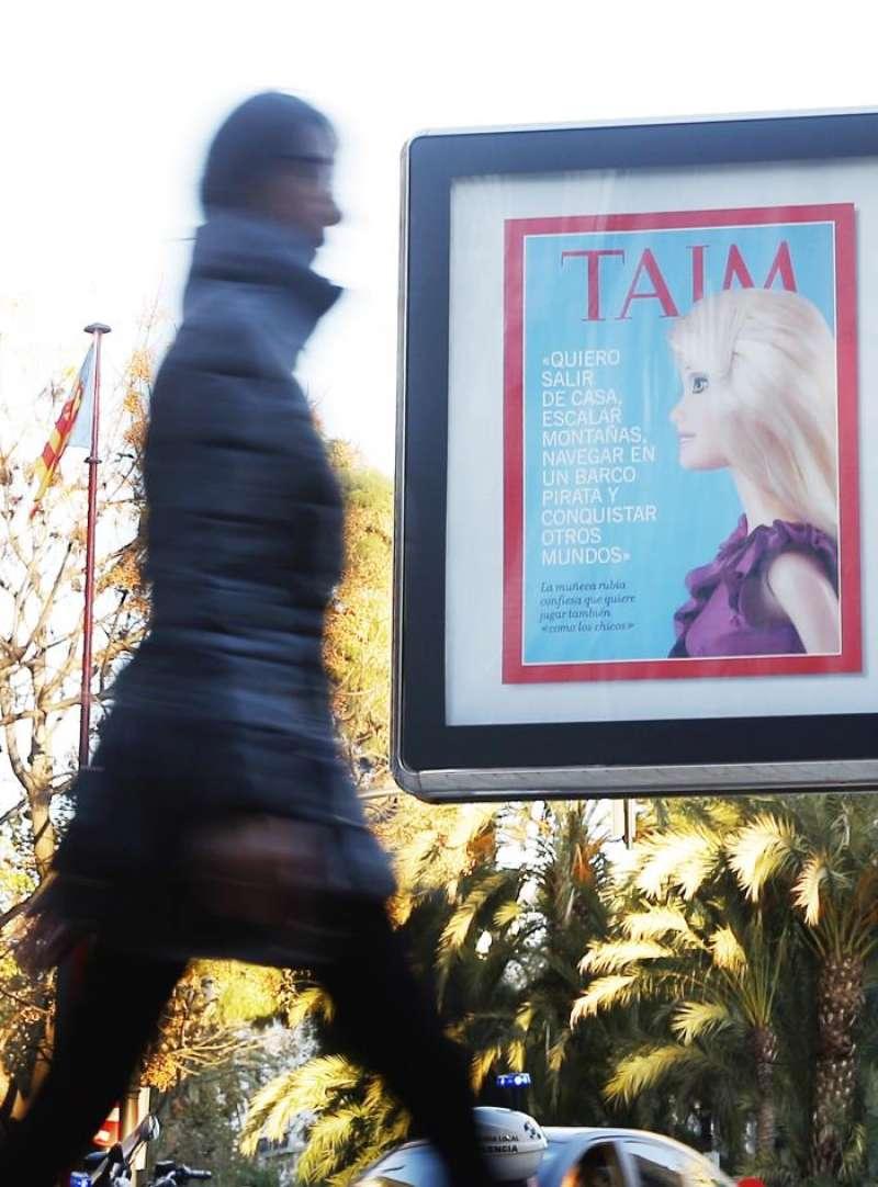 Una persona pasa ante uno de los carteles de la campaña