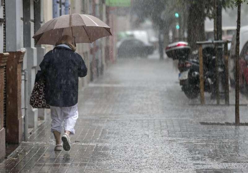 Una mujer camina bajo la lluvia. EFE/Manuel Bruque/Archivo