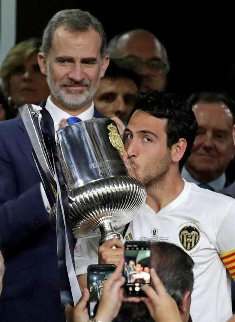 El capitán del Valencia CF, Daniel Parejo, recibe el trofeo del rey Felipe tras vencer por 2-1 al FC Barcelona en la final de la Copa del Rey. EFE/Archivo