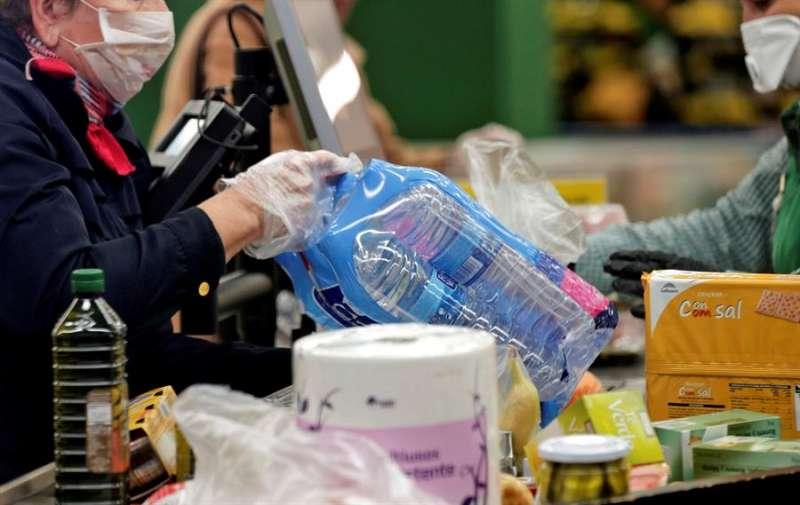 Una mujer pasa su compra por la caja de un supermercado. EFE