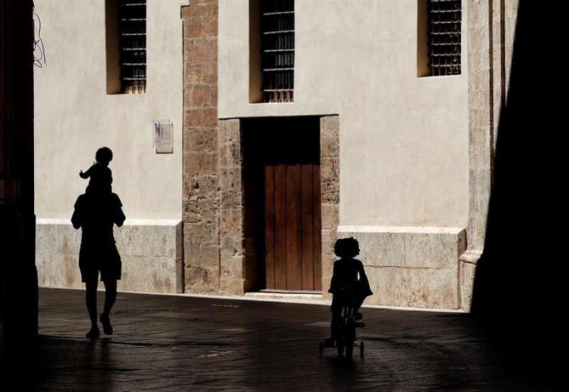 Un hombre pasea, por el centro de Valencia, junto a dos niños en el cuadragésimo quinto día de confinamiento. EFE