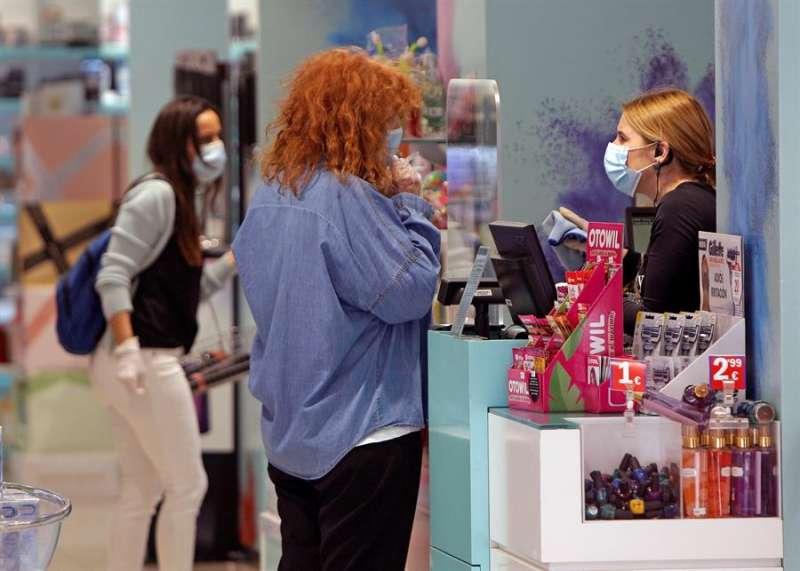Dos personas realizan una compra en una tienda en Benidorm, en fase 1 de la desescalada desde este lunes. EFE/MORELL