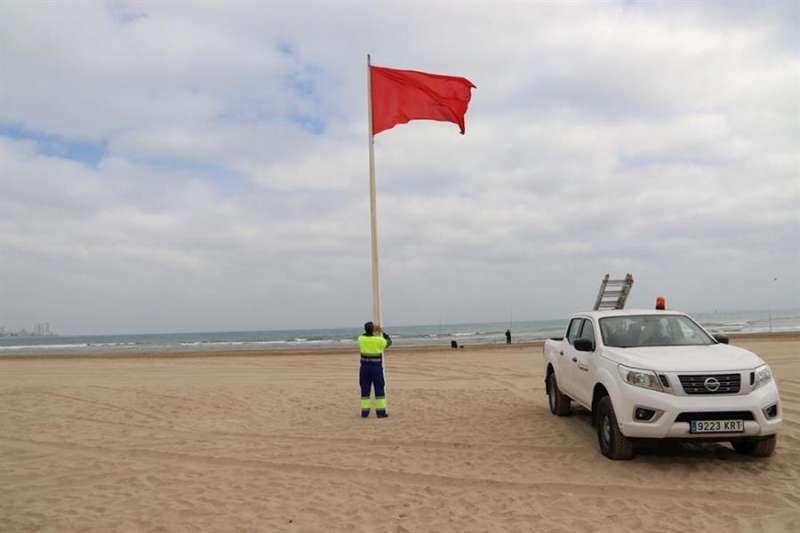 Un empleado municipal coloca una bandera roja en la playa de Cullera (Valencia), en una imagen compartida en redes sociales por el Ayuntamiento.