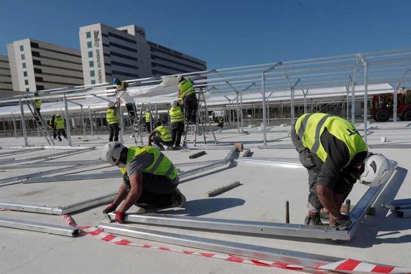 Varios operarios trabajan en la estructura del hospital de campaña de València junto al hospital La Fe. EFE
