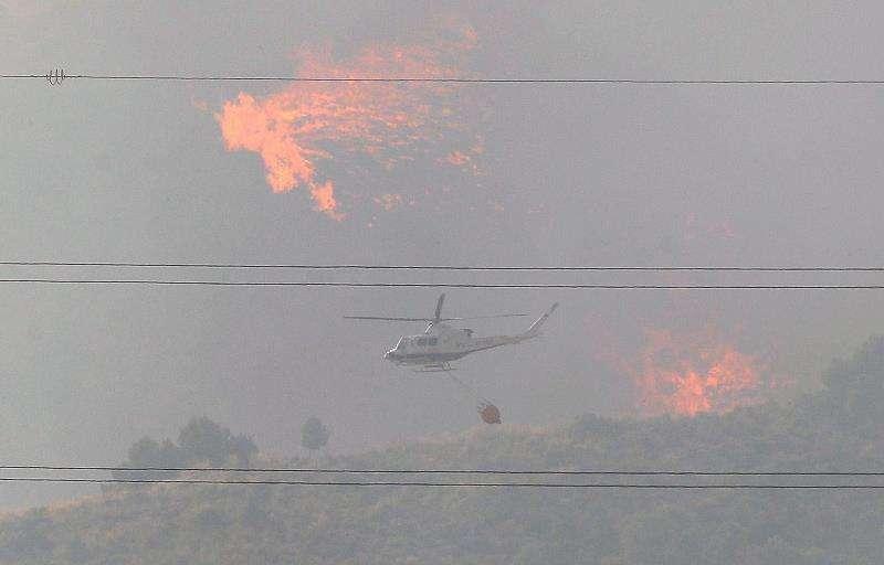 Un helicóptero trabaja en el incendio forestal declarado este lunes en una zona de barranco de Beneixama (Alicante).