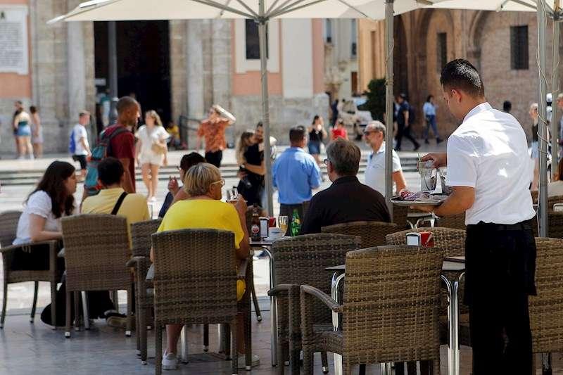 Un camarero recoge una terraza en el centro de València. EFE/Archivo/Ana Escobar